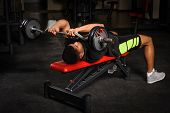 foto of bench  - handsome young african descent mixed race man doing bench french press workout with barbell in gym - JPG