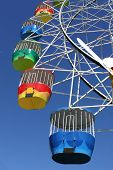 stock photo of carnival ride  - A vibrant coloured ferris wheel at an amusement park - JPG