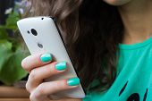 stock photo of mint-green  - female hand with bright manicure holding a cell phone. in the picture prevails green the model