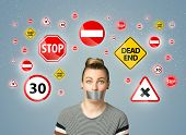 picture of traffic signal  - Young woman with taped mouth and traffic signals around her head - JPG