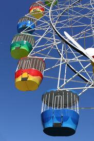 stock photo of carnival ride  - A vibrant coloured ferris wheel at an amusement park - JPG