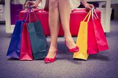 stock photo of legs crossed  - Woman sitting with legs crossed and holding shopping bags at a shoe shop - JPG