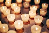 Постер, плакат: Group Of Candles In Church Candles Light Background