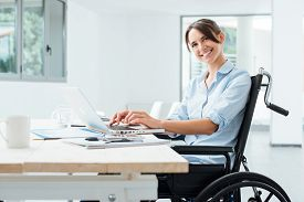 stock photo of wheelchair  - Confident happy businesswoman in wheelchair working at office desk and using a laptop she is smiling at camera disability overcoming concept - JPG