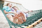 Barefoot and Relaxed family napping in a hammock together. Selective focus of two sets of feet relax poster