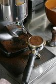 A bayonet filled with espresso grounds ready to be tamped