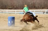 pic of barrel racing  - A young woman races to the finish after rounding a barrel - JPG