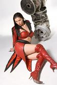 stock photo of red hair  - Pretty young woman in red leather coat lying close to metal barrels - JPG