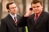 Two businessmen talking by mobile phone