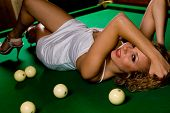 Beautiful model lying on green snooker table