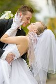 foto of wedding couple  - Colorful wedding shot of bride and groom kissing - JPG