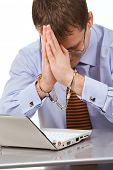 Frustrated businessman bending over laptop, handcuffs on his wrists