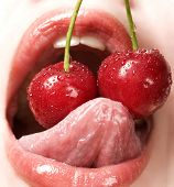 Closeup of young woman eating red cherries in very sexual manner