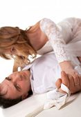 Romantic image of just married couple lying on the floor together. The groom holding a bow-tie (Focus on the bow-tie)