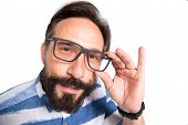 Interrogative Glance Of Smart Mature Man Looking At You While Touching The Rim Of His Glasses And Ke poster