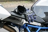 A Pair Of Gloves Of A Motor Biker On A Motor Bike poster