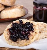 Closeup Of An English Muffin Cut In Half And Spread With Blueberry Preserves With A Jar Of Preserves poster