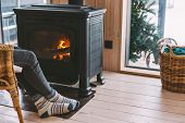 Cold fall or winter day. Woman resting by the stove. Closeup photo of human feet in warm woolen sock poster