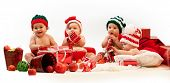 Four babies in xmas costumes playing among gifts