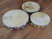 Close-up Of Three Pandeiros  (tambourines), A Brazilian Musical Percussion Instrument, On A Wooden S poster