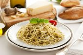 Spaghetti with Genovese pesto sauce, garnished with basil leaf and tomato, parmesan cheese and bread in background
