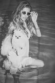 Sensual Woman With Cute Spitz Puppy In Blue Water. Girl With Small Dog In Swimming Pool. Pet, Compan poster