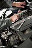 Male hand repairing car engine