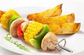 Meat skewer with corn and potatoes