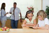 Kinder mit Tablet in der Küche mit ihren Eltern dahinter
