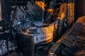 Burnt House Interior. Burned Kitchen, Remains Of Stove And Furniture In Black Soot. poster