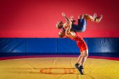 The Concept Of Fair Wrestling. Two Greco-roman  Wrestlers In Red And Blue Uniform Wrestling   On A Y poster