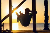 Man Relaxes In A Hammock On Abandoned Bungalow Veranda, Admiring The Turquoise Sea During Sun Set. A poster