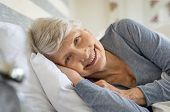 Smiling senior woman resting on bed and looking at camera. Awaken old woman with grey hair and pajam poster