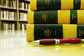 picture of law-books  - Law books stacked with pen in a library - JPG