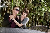 Happy young romantic couple wearing sunglasses on patio