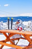 picture of apr  - Apres ski in Sarikamis. Beautiful skier waiting for order in cafe on top of mountain.
