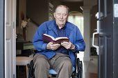 Elderly Man In Wheelchair At His Front Door Reading The Bible