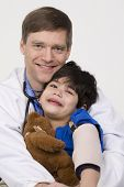 Doctor holding little patient in arms