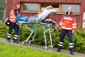Paramedics with patient on emergency stretcher ambulance aid woman man