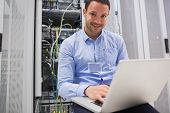 Happy man using laptop to check servers in data center