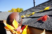 pic of gutter  - Rain gutter full of autumn leaves with a football - JPG