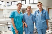 Three smiling nurses leaning against railing at hospital stairwell