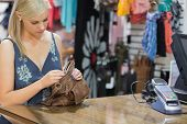 Woman standing at the counter looking through handbag in boutique