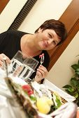 stock photo of drinking water  - Happy woman has dinner in fish restaurant - JPG