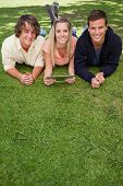 Portrait of three young people using a tactile tablet while lying in a park