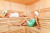Two young woman relaxing in sauna