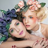 Two Pretty Girls Blonde And Brunette In Colored Wreaths Hugging