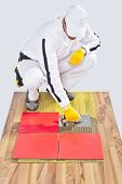 Worker Applies Ceramic Tiles On Wooden Floor With Notched Trowel