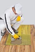 Worker Applies Tile Adhesive With Reinforcement Mesh On Wooden Floor