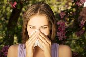 Young woman with allergy during sunny day is wiping her nose.